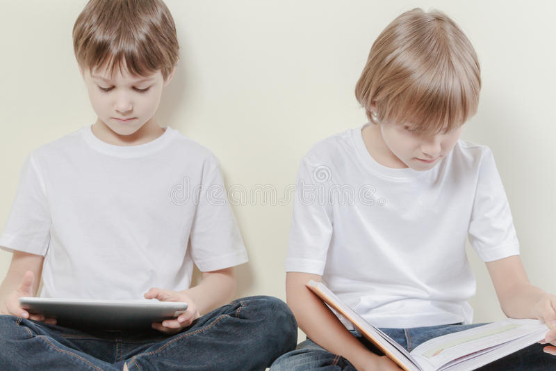 Menino com o tablet pc e a criança que leem um livro Caçoa o conceito do lazer da educação imagens de stock