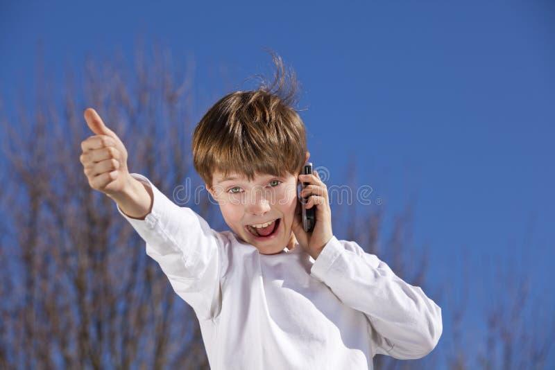 Menino com o telefone de pilha que levanta os polegares acima imagens de stock