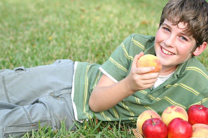 Menino com pêssegos & maçãs imagem de stock royalty free