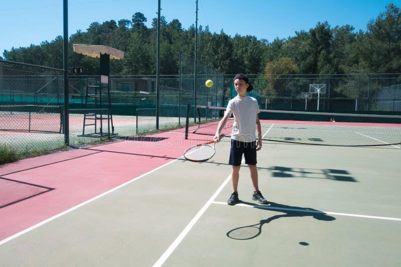 Menino com a raquete na área do tênis imagem de stock