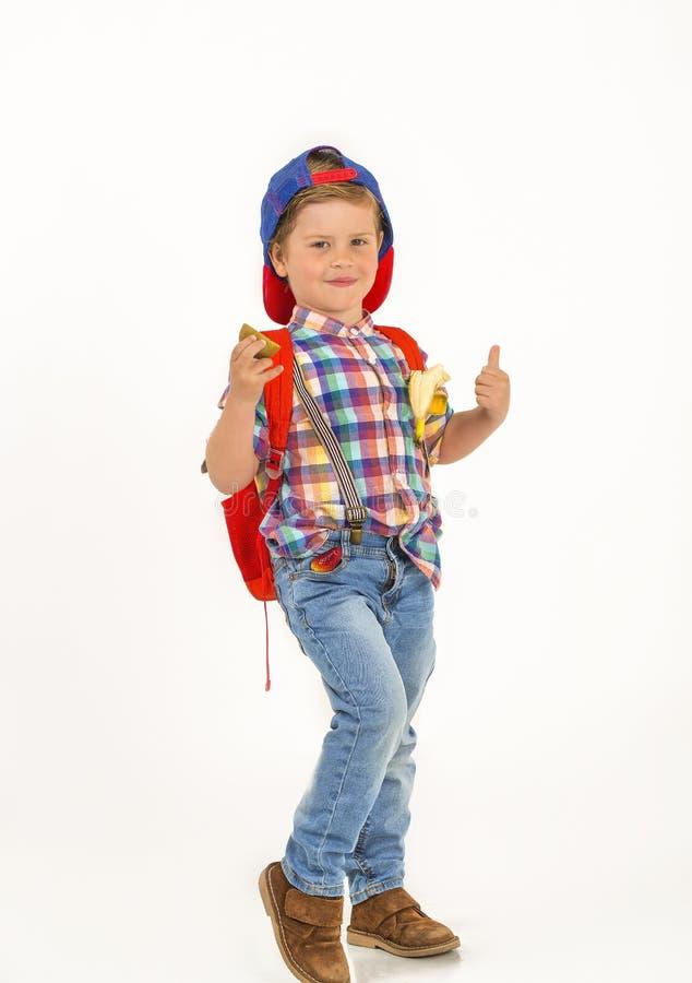Menino com tampão e trouxa com fruto em seus bolsos fotos de stock royalty free