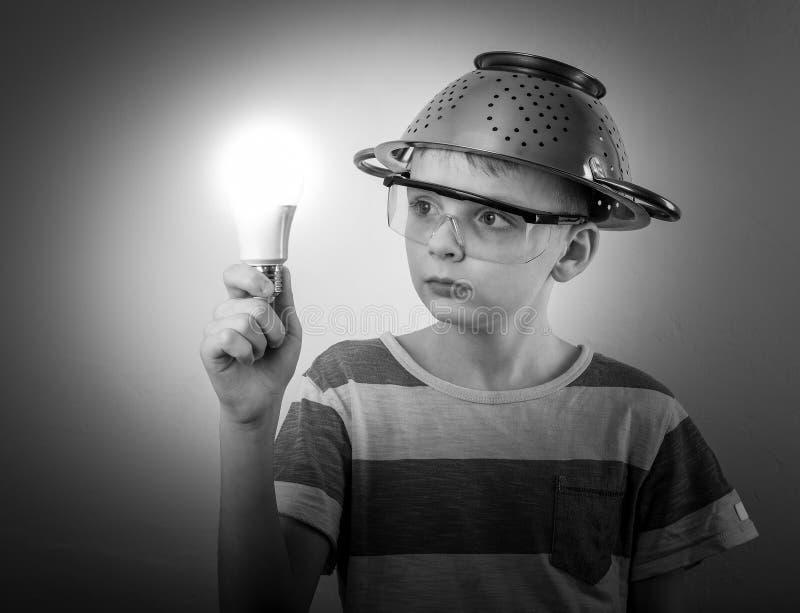 Menino com um bulbo iluminado na mão fotos de stock royalty free