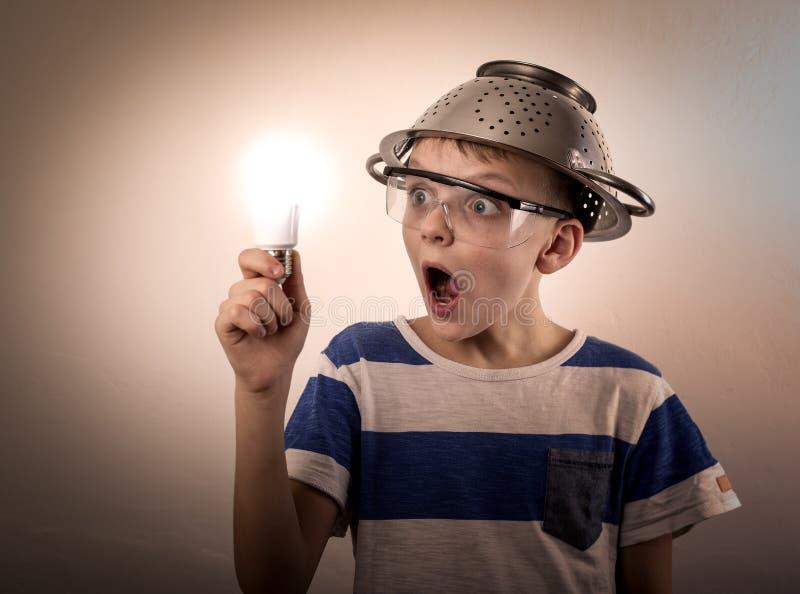 Menino com um bulbo iluminado na mão fotografia de stock