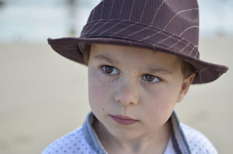 Menino com um chapéu marrom que olha muito sério fotos de stock