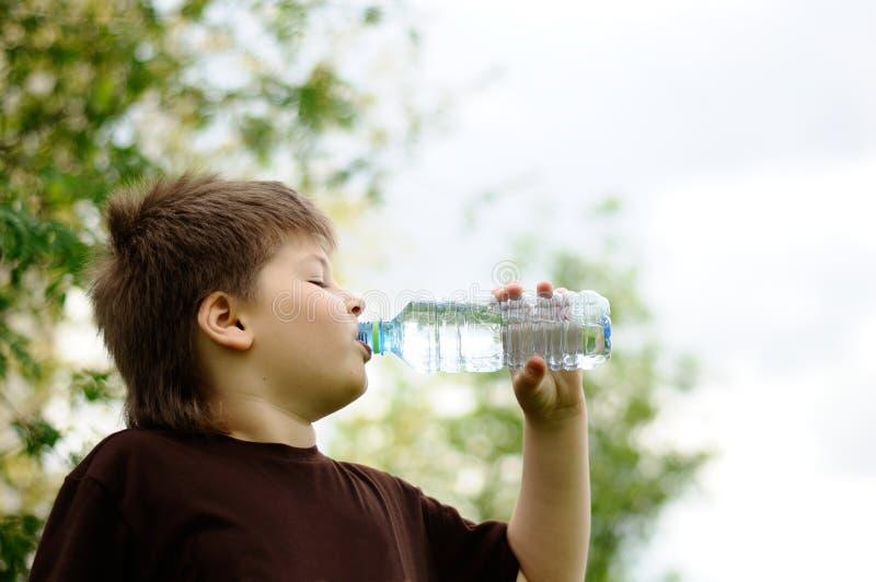 Menino com um frasco da água na natureza fotografia de stock
