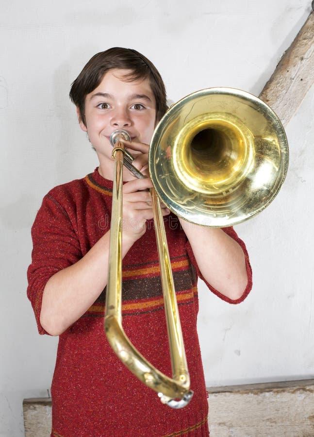 Menino com um trombone imagens de stock