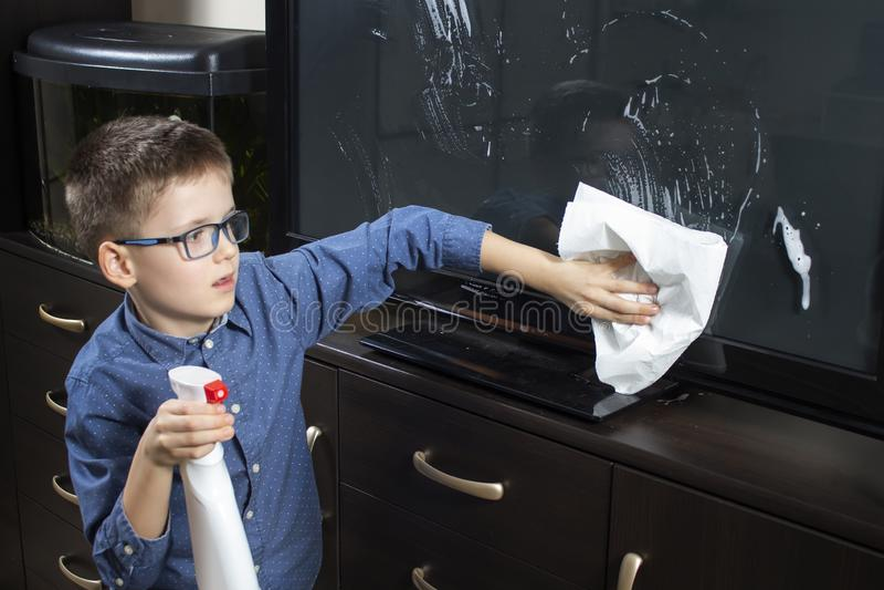 Menino com vidros durante a limpeza Limpa a tela da tevê com a poeira do pano imagens de stock royalty free