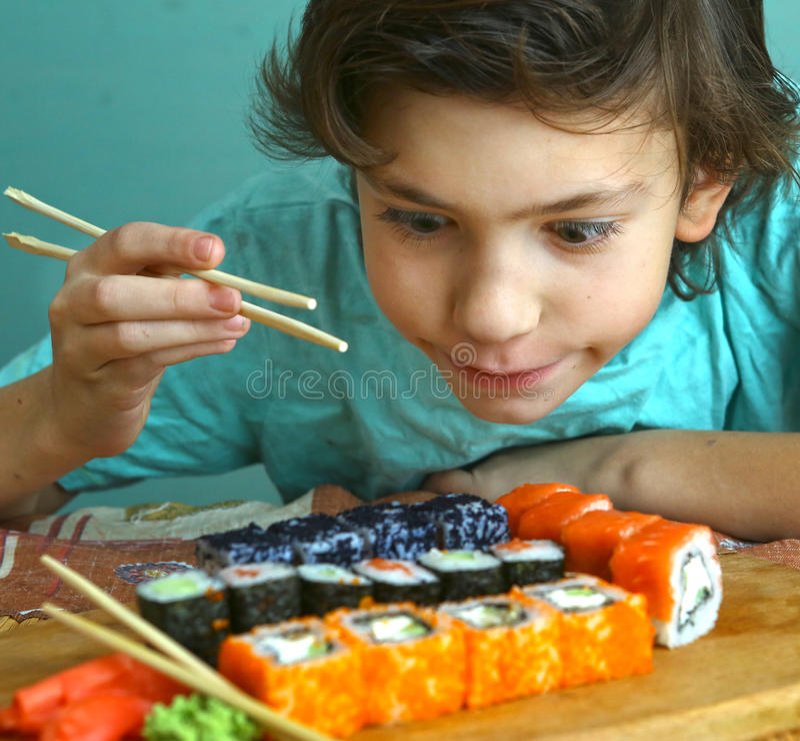 Menino considerável do Preteen com grupo do rolo de sushi foto de stock royalty free