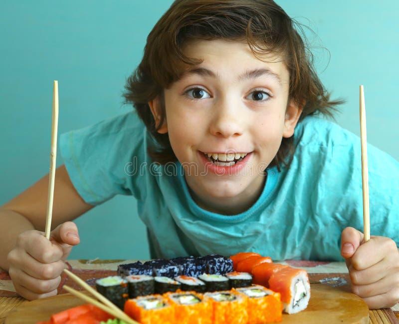 Menino considerável do Preteen com grupo do rolo de sushi imagens de stock