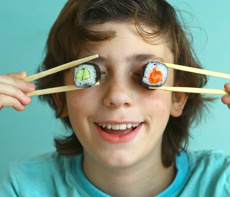 Menino considerável do Preteen com grupo do rolo de sushi foto de stock
