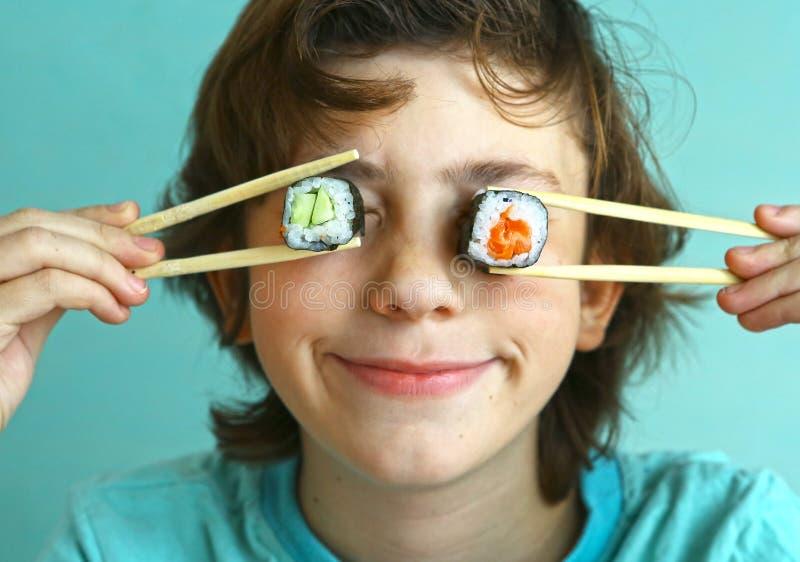 Menino considerável do Preteen com grupo do rolo de sushi imagem de stock
