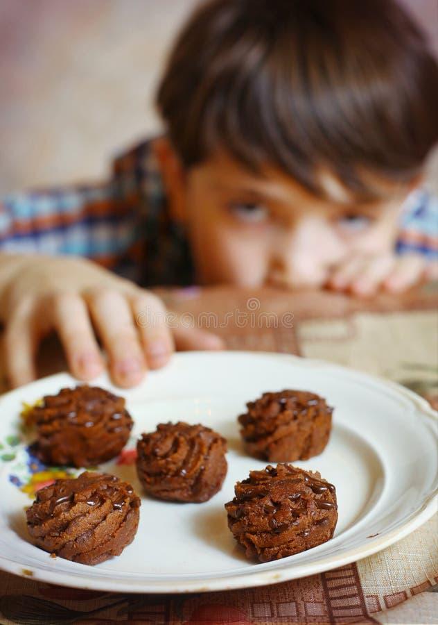 Menino considerável do Preteen com os doces do chokolate na placa fotografia de stock