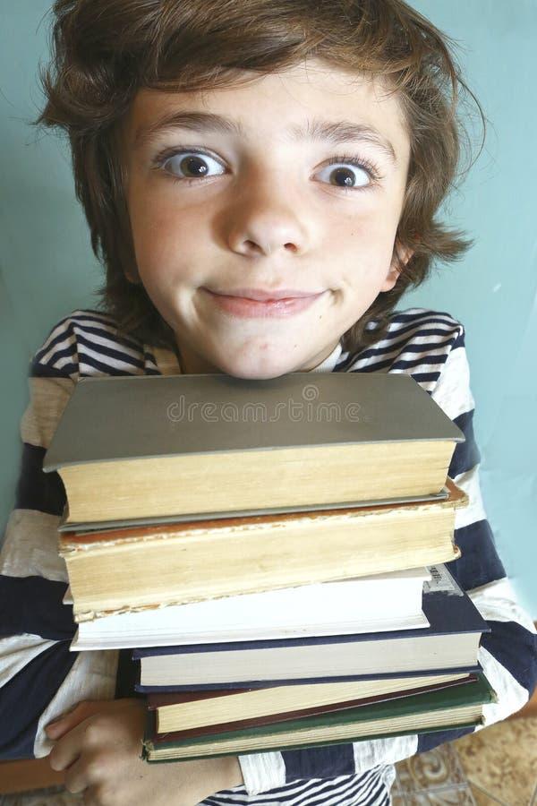Menino considerável do Preteen com pilha do livro fotos de stock
