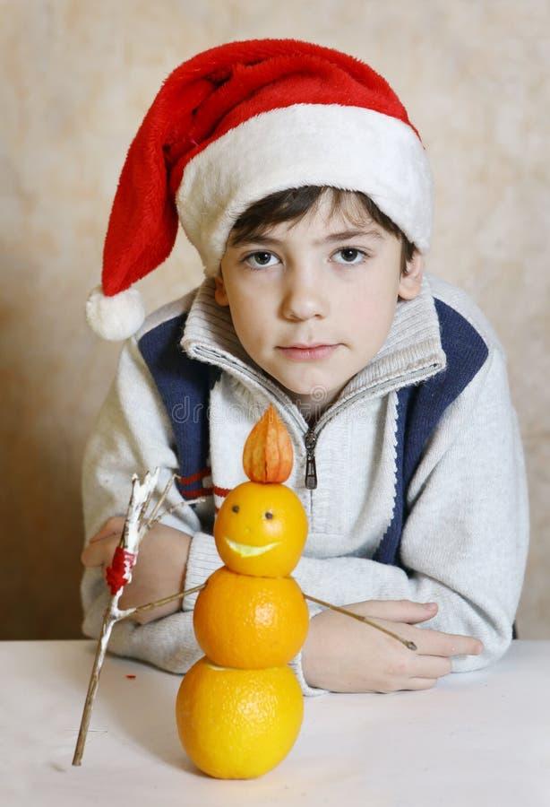 Menino considerável do preteen no chapéu de Santa com boneco de neve das laranjas foto de stock