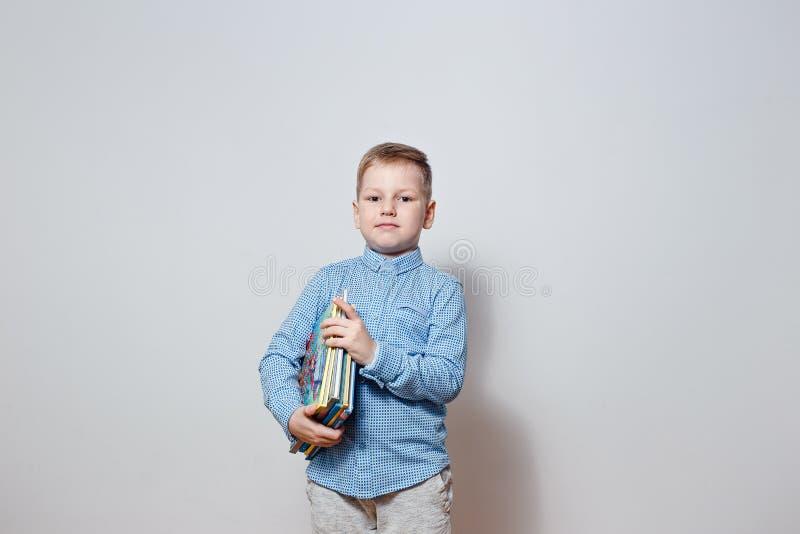 Menino considerável em uma camisa azul que guarda o livro sob seu braço foto de stock royalty free