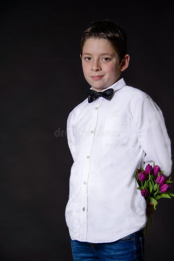 Menino considerável na camisa branca e no bowtie preto que guardam um ramalhete das tulipas no fundo preto Conceito para a mola e fotografia de stock