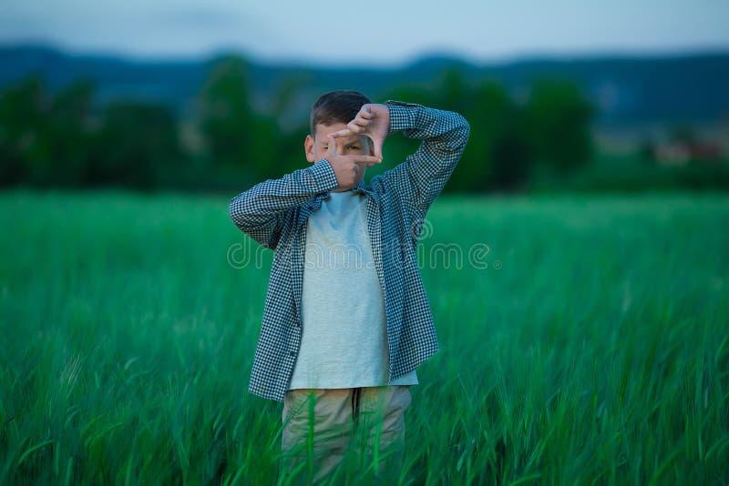 Menino considerável pequeno bonito que levanta com os dedos da câmera que vestem a roupa acolhedor e que estão no centeio fresco  foto de stock royalty free