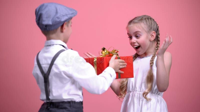 Menino considerável surpreendente sua amiga pequena com giftbox, celebração do aniversário foto de stock royalty free