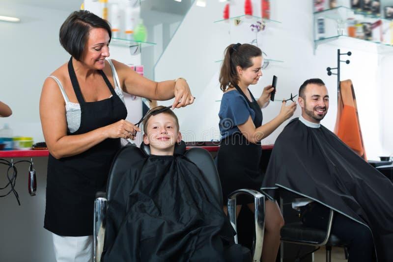 Menino contente que senta-se na cadeira e que obtém o corte do cabelo fotografia de stock royalty free