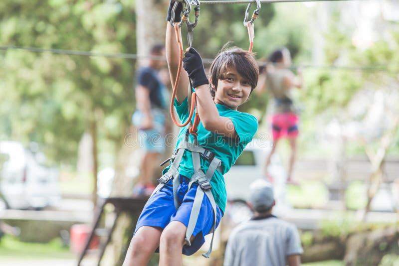 Menino corajoso ativo que aprecia a escalada de partida no parque da aventura sobre foto de stock
