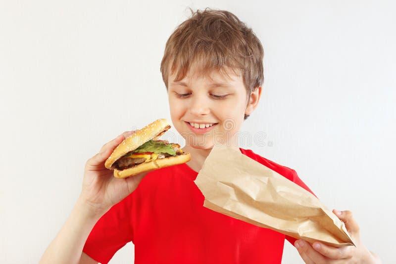 Menino cortado pequeno para remover um Hamburger grande de um pacote de papel no fundo branco fotos de stock