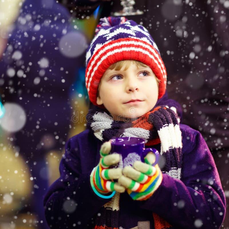 Menino da criança com chocolate quente no mercado do Natal imagem de stock royalty free