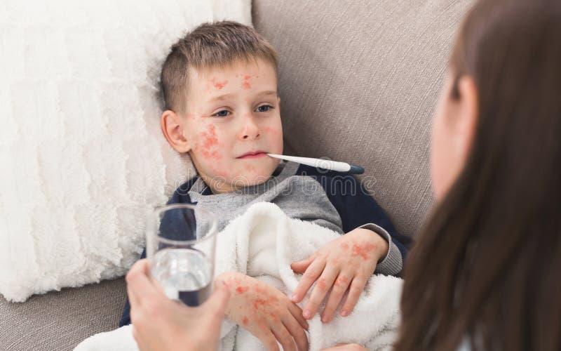 Menino da criança com a temperatura de medição do sarampo, encontrando-se no sofá fotografia de stock