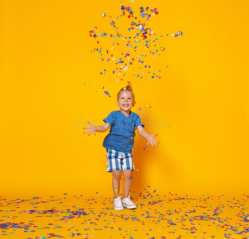 Menino da criança do feliz aniversario com confetes no fundo amarelo fotos de stock royalty free