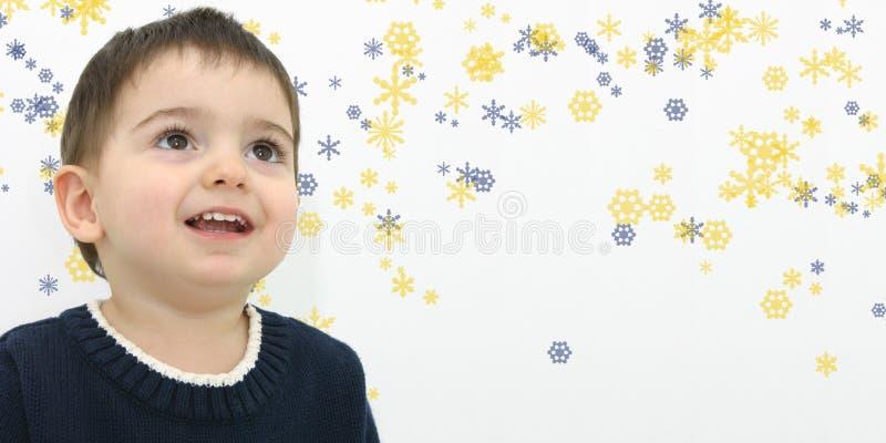 Menino da criança do inverno no fundo do floco de neve fotos de stock