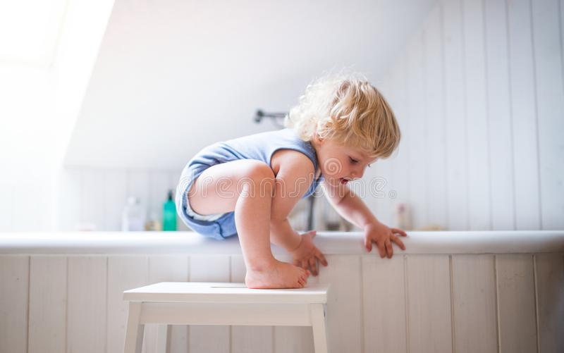 Menino da criança em uma situação perigosa no banheiro foto de stock