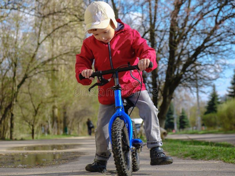 Menino da criança da equitação com sua primeira bicicleta no parque da cidade Criança feliz na roupa colorida Lazer para crianças foto de stock royalty free