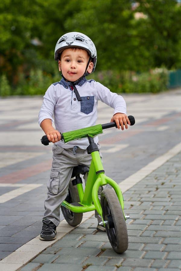 Menino da criança na equitação branca do capacete em sua primeira bicicleta com um capacete bicicleta sem pedais foto de stock