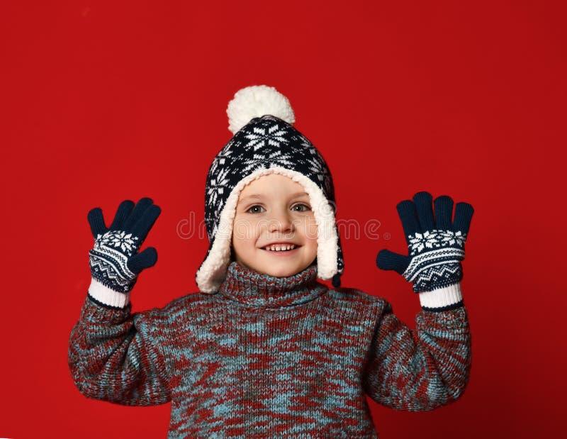 Menino da criança no chapéu feito malha e camiseta e mitenes que têm o divertimento sobre o fundo vermelho colorido fotografia de stock royalty free