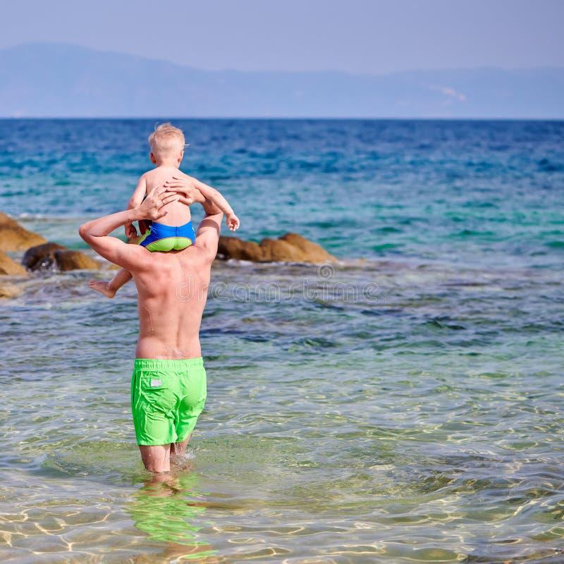 Menino da criança nos ombros do pai na praia imagem de stock royalty free