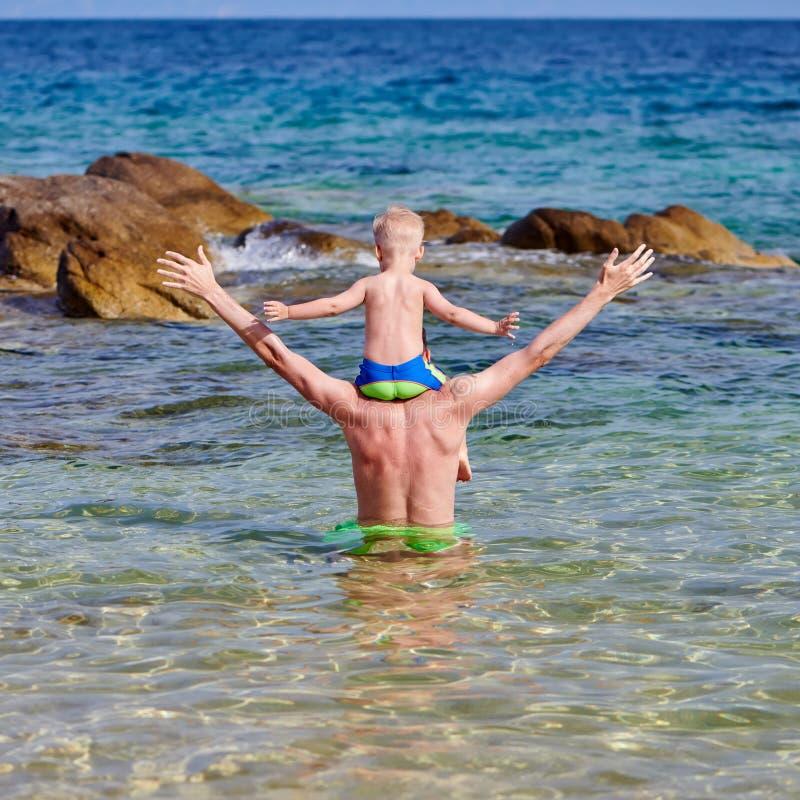 Menino da criança nos ombros do pai na praia fotografia de stock royalty free
