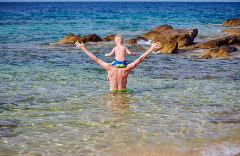 Menino da criança nos ombros do pai na praia fotografia de stock