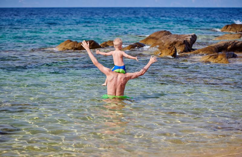 Menino da criança nos ombros do pai na praia fotos de stock