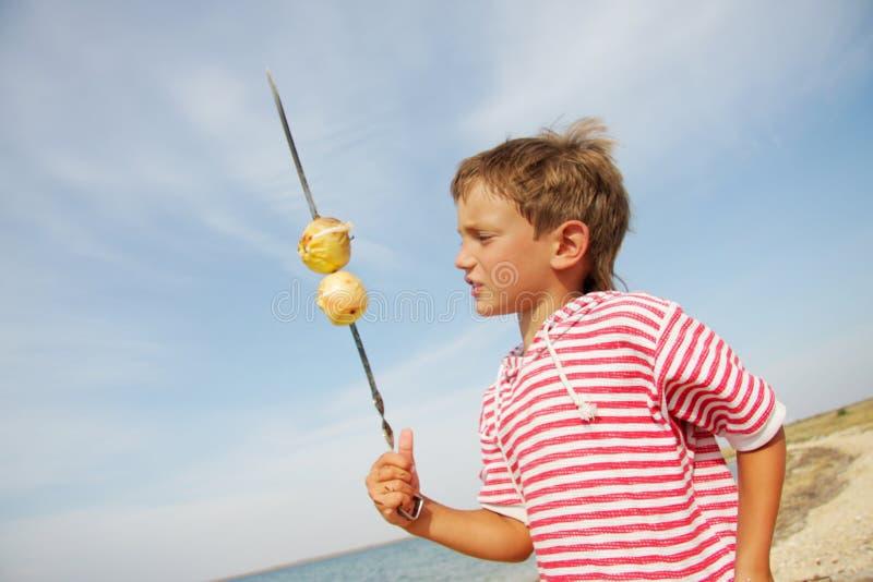 Menino da criança nova com maçãs grelhadas foto de stock royalty free