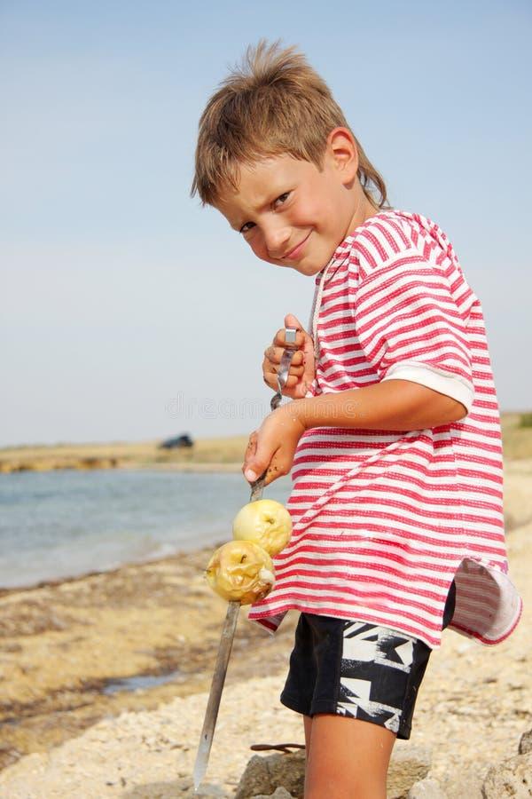 Menino da criança nova com maçãs grelhadas fotografia de stock