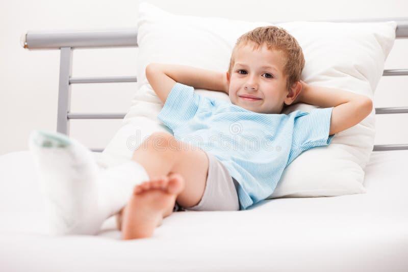 Menino da criança pequena com a atadura do emplastro na fratura ou no Br do salto do pé imagem de stock royalty free