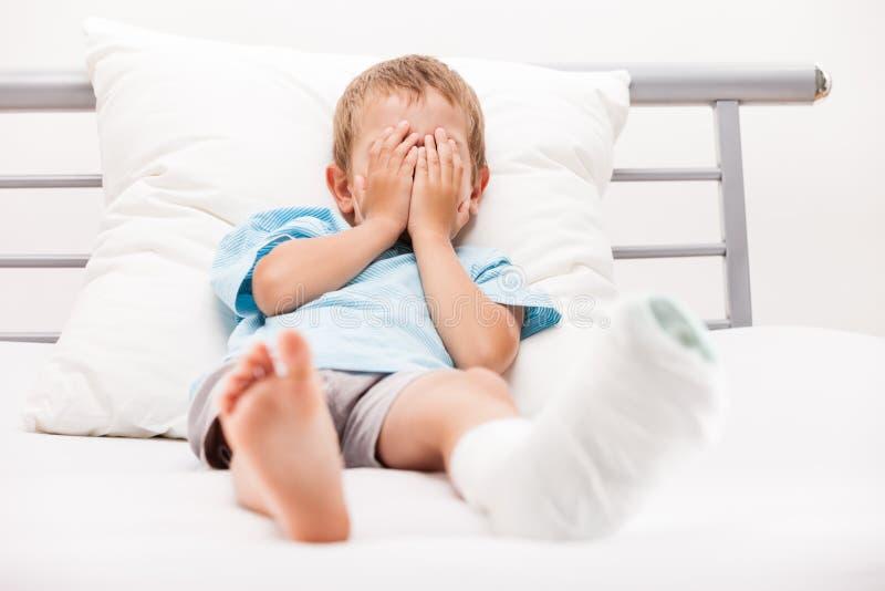 Menino da criança pequena com a atadura do emplastro na fratura ou no Br do salto do pé foto de stock