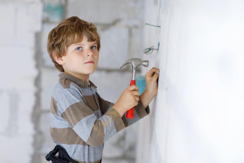Menino da criança que ajuda com as ferramentas do brinquedo no canteiro de obras Criança engraçada de 6 anos que têm o divertimen imagens de stock royalty free