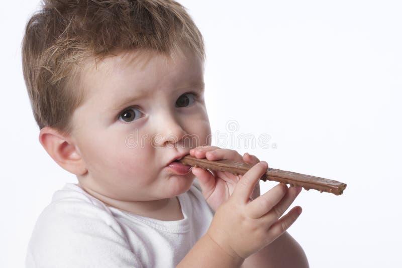 Menino da criança que come doces imagem de stock