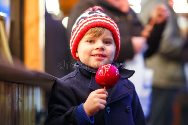Menino da criança que come a maçã doce no mercado do Natal imagem de stock royalty free