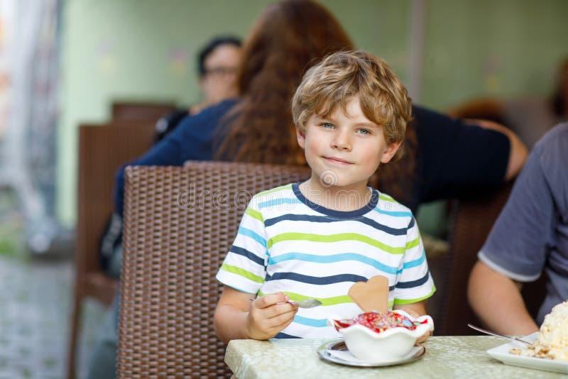 Menino da criança que come o gelado no café ou no restaurante exterior foto de stock royalty free