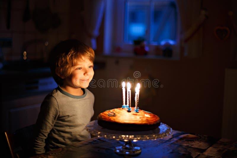 Menino da criança que comemora seu aniversário e que funde velas no bolo foto de stock royalty free