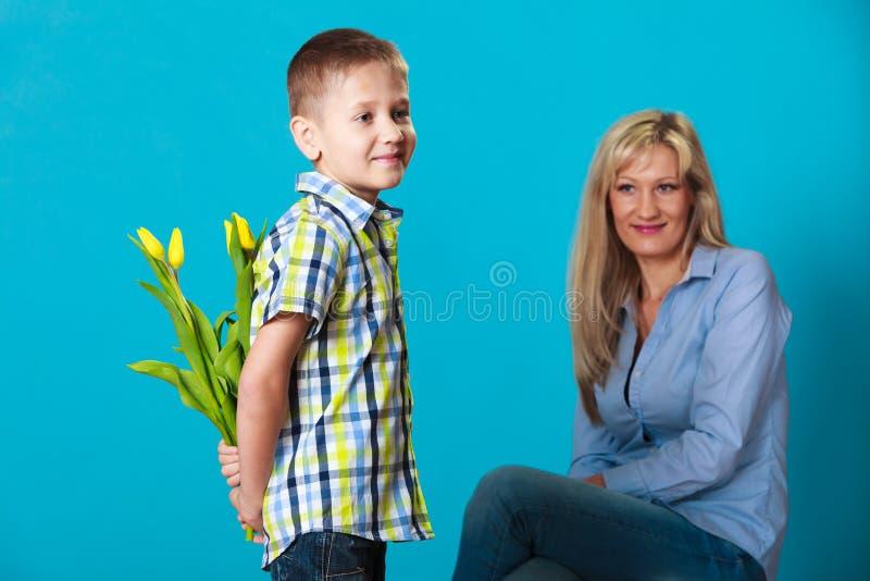 Menino da criança que dá a flores sua mãe fotografia de stock