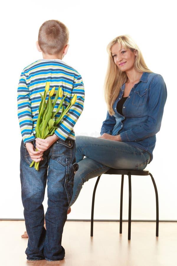 Menino da criança que dá a flores sua mãe foto de stock royalty free