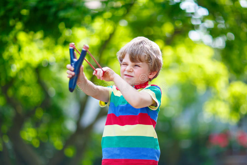 Menino da criança que dispara no estilingue de madeira fotos de stock