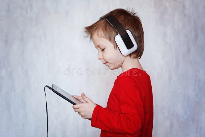 Menino da criança que escuta a música ou o filme de observação com fones de ouvido a imagem de stock royalty free